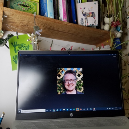 Image: A laptop with a pending Zoom call sits on a desk cluttered with personal items desk